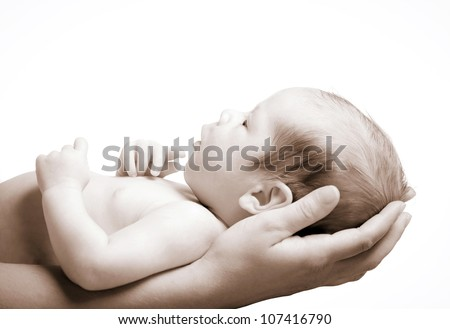 Little baby held in mom's hands, sepia tone image - stock photo
