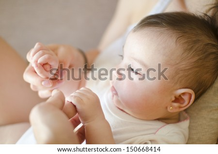 Little baby holding mother hands - stock photo