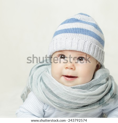 Little baby in blue hat and scarf - stock photo