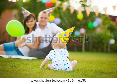 Little baby in cap on his birthday with parent on background