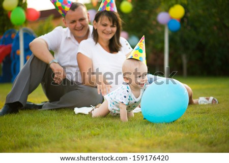 Little baby in cap on his birthday with parent on background - stock photo