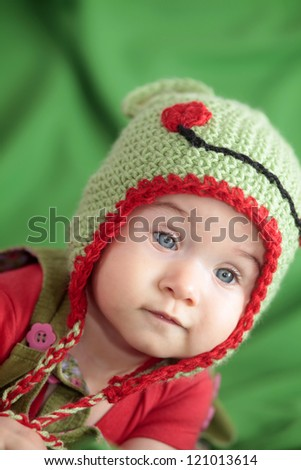 Little baby in hand knit hat - stock photo