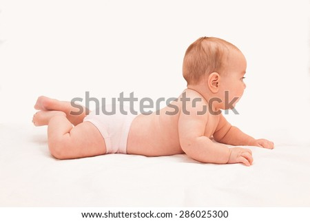 Little baby in pants laying on his tummy with his head up, trying and learning to crawl on light sheet background. Side view. - stock photo