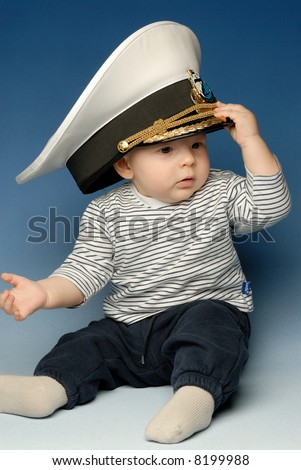 Little baby in sailor's cloths with captain's hat on his head - stock photo