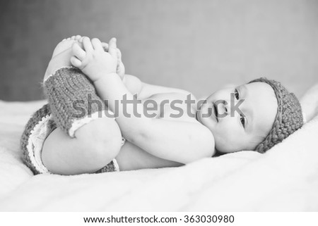 little baby is laying and catching own legs - stock photo