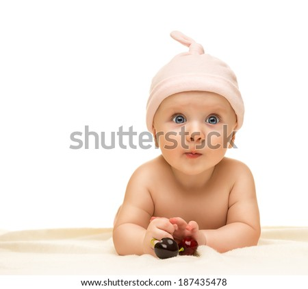 Little baby is looking into the camera and is wearing a hat on the white background