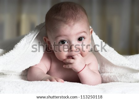 Little baby is lying in bed with fingers in mouth - stock photo