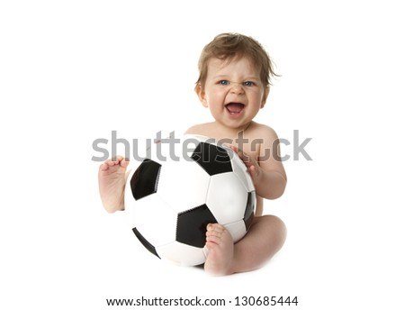 Little baby is playing with a football. He is very happy. - stock photo