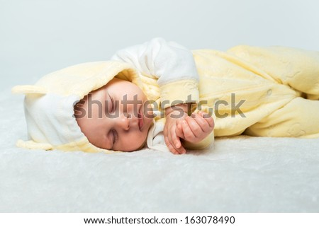 Little baby is sleeping on the white carpet - stock photo