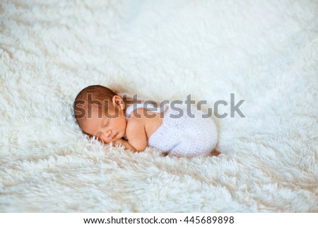 Little baby is sleeping on the white fur - stock photo