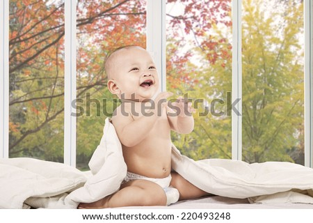 Little baby laughing alone on bedroom at home with autumn tree background - stock photo