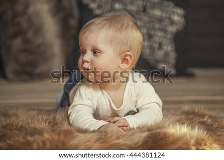 Little baby lying on a fur rug at home closeup portrait