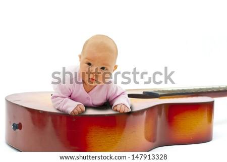 little baby lying on guitar - stock photo