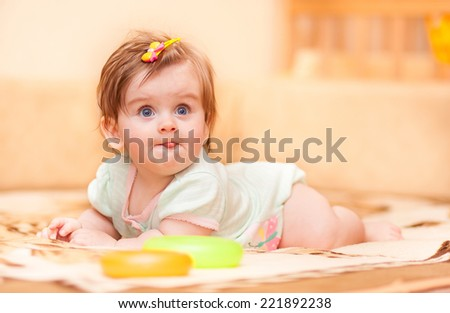 little baby lying on the blanket and showing tongue - stock photo