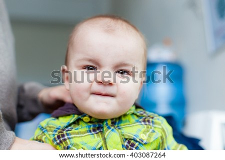 Little baby makes faces at the background of water cooler, closeup portrait, smiling, nice, pretty - stock photo