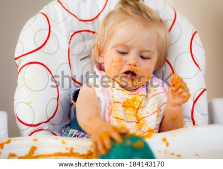 Little baby making a mess with food - stock photo