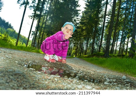 little baby near small puddle - stock photo