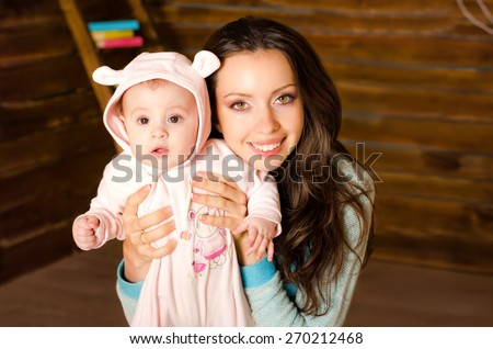 little baby on hands at mum.The colorful decorations made of wood and toys. Easter theme - stock photo