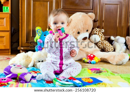 little baby on the play mat with toys smiling - stock photo