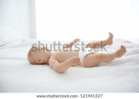 Little baby on white bed in room