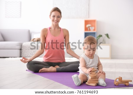 Little baby playing and mother doing yoga at home
