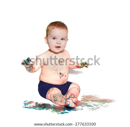 little baby playing with bright colors, getting messy hands and face. On white background - stock photo