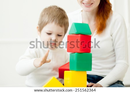 Little baby playing with colorful toy plastic blocks. Building a tower. Focus on child - stock photo
