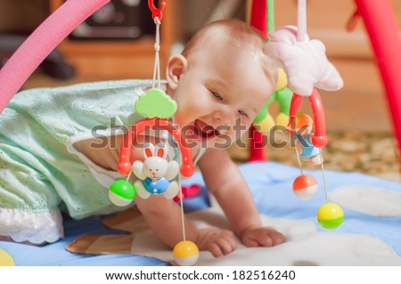 little baby playing with toys at home - stock photo