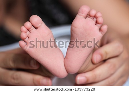 Little baby's feet with mom
