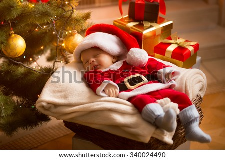 Little baby Santa sleeping under Christmas tree with presents