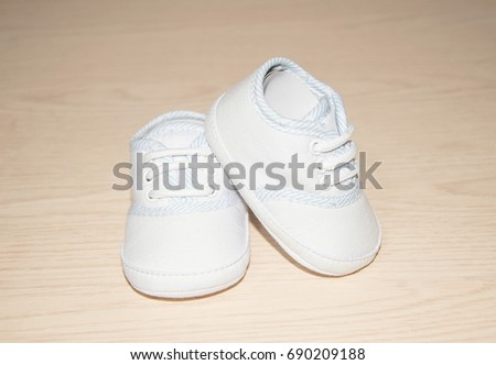 Little baby shoes isolated on a wooden background