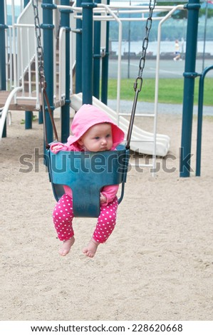 Little baby sits in the swing and waits for someone to give her a push - stock photo