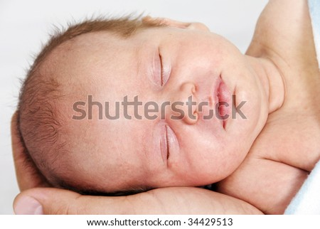 Little baby sleeping in his daddy's hand - stock photo