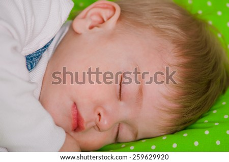 Little baby sleeping on a green cushion