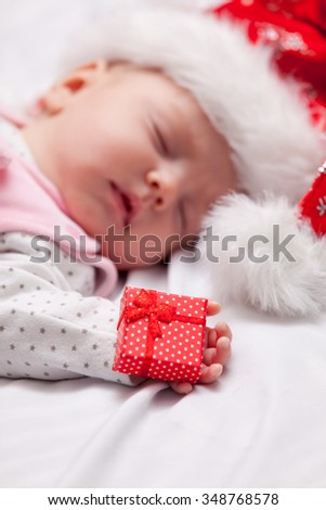 Little baby sleeping with christmas gifts on a white background - stock photo