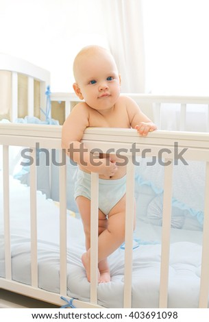 Little baby standing on the bed at home - stock photo