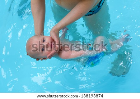 Little baby swimming in water - stock photo