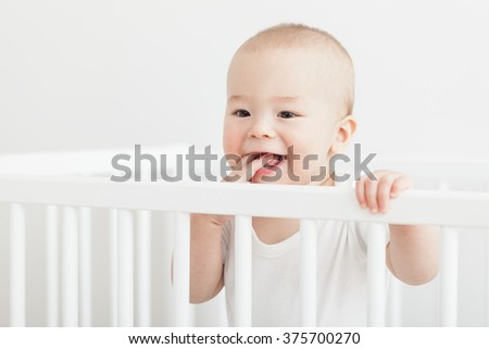 Little baby teething, white crib. - stock photo