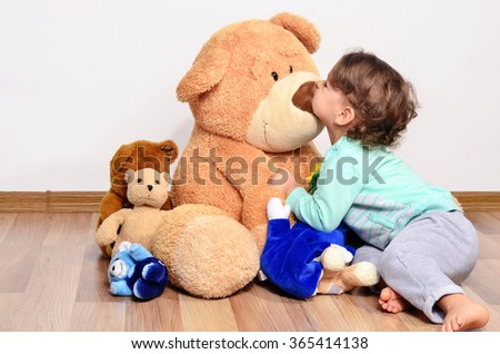 Little baby toddler playing with his teddy bears. Cute boy loving and kissing his big teddy bear toy. - stock photo