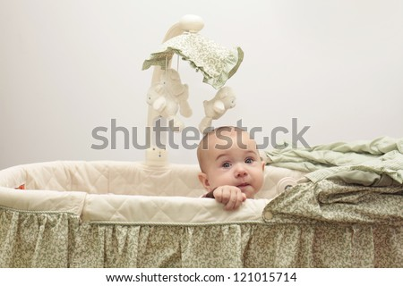 Little baby trying to get out from the crib - stock photo