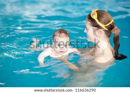 Little baby with blue eyes learning to swim - stock photo