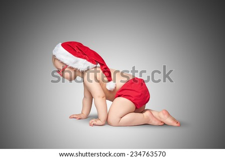 little baby with Santa hat and glasses crawling on gray background. - stock photo