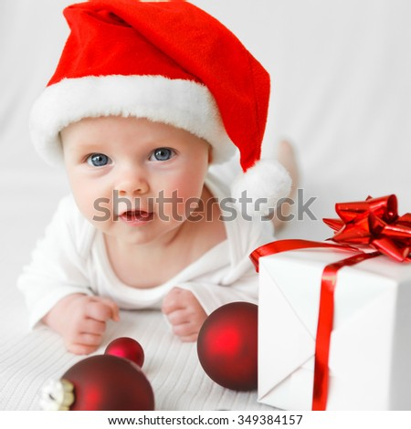 little baby with santas hat and a gift