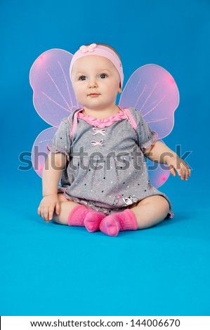 little baby with wings sitting on a blue background