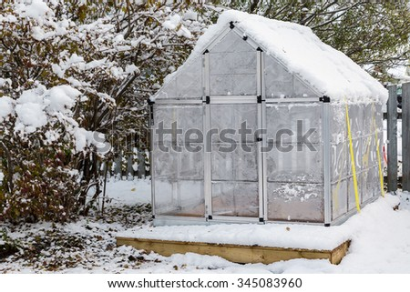 Little back yard home greenhouse in the snow. - stock photo