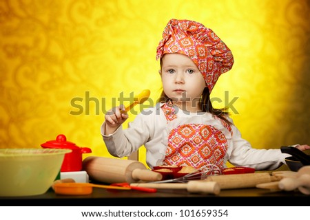 Little baker or cook girl cuts dough for cookies on kitchen with form - stock photo
