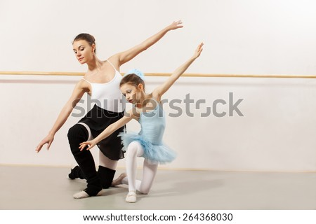 Little ballerina dancing with ballet teacher in dance studio. They both wearing a white tutu and leotard - stock photo