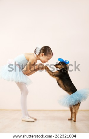 Little ballerina dancing with her cute dog in dance studio. They both wearing a tutu - stock photo