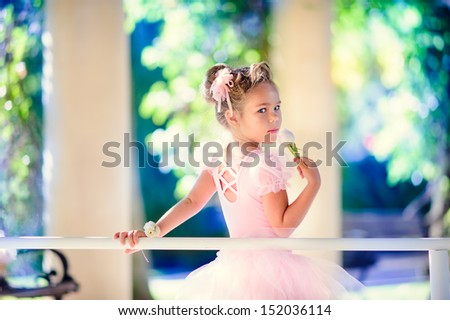 Little ballerina girl doing ballet bar exercises with flower on her hand at beautiful garden background - stock photo