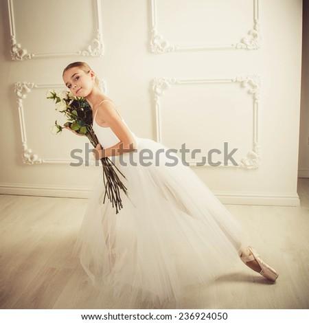 Little ballerina girl in a dress, classical, ballet dance. A girl in a ball gown sitting on sofa classic, white background, white sofa classic. - stock photo